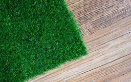 Künstlicher Rasen auf hölzerner Fliese Stockfotografie