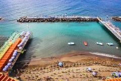Künstlicher Sandstrand Sorrent-Sommers mit Steinen von Wellenbrechern auf ruhigem blauem Meer Italien Stockfotografie