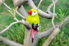 Künstlicher Vogel, der auf Baum sitzt Stockfoto