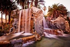 Künstlicher Wasserfall mit Palmen Stockfotografie