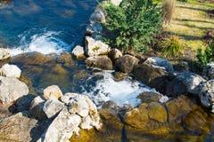 Künstlicher Wasserfall am Vorfrühlingsmorgen Stockfoto
