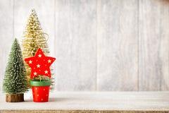 Künstlicher Weihnachtsbaum auf einem hölzernen Hintergrund Lizenzfreies Stockbild