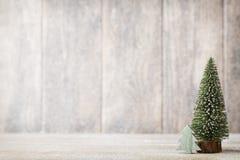 Künstlicher Weihnachtsbaum auf einem hölzernen Hintergrund Lizenzfreie Stockbilder