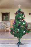 Künstlicher Weihnachtsbaum mit dekorativen Bällen und einem Stern Stockfoto