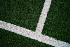 Künstliches dunkelgrünes Gras mit einer diagonalen umgedrehten winkligen t-Linie lizenzfreies stockbild