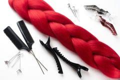 Künstliches Haar rot auf weißer naher COM clipso Draufsicht des Hintergrundes lizenzfreies stockbild