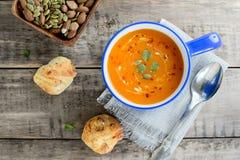 Kürbis- und Karottensuppe mit Nüssen und Brotbrötchen auf rustikalem hölzernem Hintergrund Lizenzfreie Stockfotografie