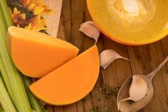 Kürbis- und Karottensuppe mit Sahne und Petersilie auf dunklem Holztisch mit selery, garlick und Stücken des Kürbises stockbilder