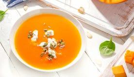 Kürbis- und Karottensuppe mit Sahne und Samen auf weißem hölzernem BAC lizenzfreies stockfoto