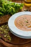 Kürbis- und Karottensuppe mit Samen in einer weißen Platte auf dem hölzernen Hintergrund stockfoto