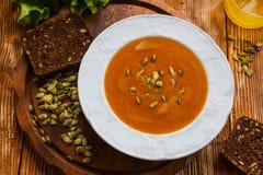 Kürbis- und Karottensuppe mit Samen in einer weißen Platte auf dem hölzernen Hintergrund lizenzfreie stockbilder