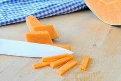 Kürbis und keramisches Messer auf hölzernem Brett Stockfotos