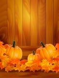 Kürbise auf hölzernem Hintergrund mit Blättern Lizenzfreie Stockbilder
