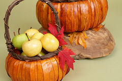 Kürbise und Äpfel in den Körben auf hölzerner Bank Lizenzfreie Stockfotos
