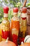 Kürbise und buntes in Essig eingelegtes Gemüse, wenn Glas konserviert wird Lizenzfreie Stockbilder