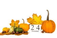 Kürbise und Herbstlaub mit Datum am 24. November, Danksagung Stockfotografie