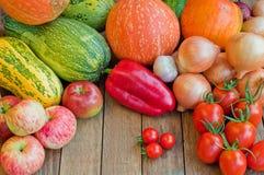 Kürbise, Zwiebeln, Tomaten und anderes Gemüse auf hölzernem backgr stockbild