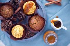 Kürbisgewürzkleiner kuchen mit buttercream und Kürbissirup nahe bei Muffin auf konkretem grauem rundem Behälter auf blauer Servie Stockfoto
