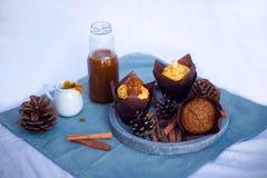 Kürbisgewürzkleiner kuchen mit buttercream und Kürbissirup nahe bei Muffin auf konkretem grauem rundem Behälter auf blauer Servie Stockbild