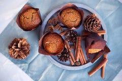 Kürbisgewürzkleiner kuchen mit buttercream und Kürbissirup nahe bei Muffin auf konkretem grauem rundem Behälter auf blauer Servie Lizenzfreie Stockfotos
