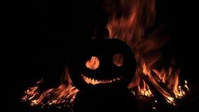 Kürbiskopf mit einem toothy Lächeln auf dem Hintergrund des Feuers stock video