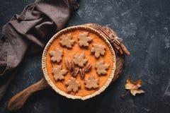 Kürbiskuchen verziert mit Lebkuchengewürzplätzchen und Pekannüssen Stockbilder
