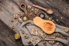 Kürbisnüsse und -plätzchen mit Samen auf Holztisch Stockbilder
