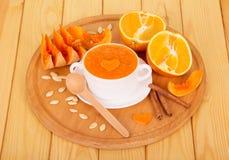 Kürbispüree in einer weißen Terrine, in einer geschnittenen Orange und in einer Vanille haftet auf hellen hölzernen Planken Stockfotos