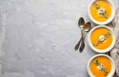 Kürbissuppe auf grauem konkretem Hintergrund Stockfotografie