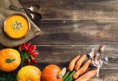 Kürbissuppe auf hölzernem Hintergrund Stockbild