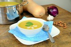 Kürbissuppe auf hölzerner Tabelle mit Bestandteilen Stockfotos