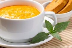 Kürbissuppe in einer Schüssel mit frischem Basilikum Lizenzfreie Stockfotos