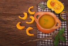 Kürbissuppe im Tongefäß mit frischen Kürbisen Lizenzfreie Stockbilder