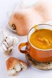 Kürbissuppe mit Brot, Knoblauch und Kürbis auf weißem Hintergrund Lizenzfreie Stockfotografie