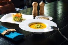 Kürbissuppe mit Getreidebrot Stockbilder