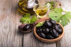 Kürzlich geerntete Olivenbeeren in den hölzernen Schüsseln und in gepresstem Öl in den Glasflaschen Stillleben der Lebensmittelzu lizenzfreie stockfotos