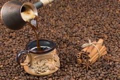Kürzlich gemachter Kaffee wird aus dem Kaffeetopf in die Schale gegossen Stockfoto