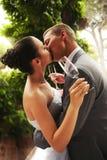 Küssen der Braut und des Bräutigams mit Gläsern lizenzfreie stockfotos