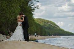 Küssen der Hochzeitspaare auf Strand Stockfotografie