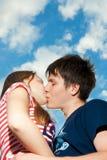 Küssen der Paare auf einem Hintergrund des blauen Himmels Lizenzfreies Stockbild