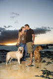 Küssen der Paare mit Hunden am Strand Lizenzfreies Stockfoto