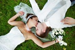 Küssen Sie die Braut und den Bräutigam am Hochzeitsweg Lizenzfreie Stockfotos