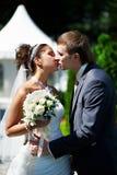 Küssen Sie glückliche Braut und Bräutigam am Hochzeitsweg im Park Stockbild