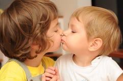 Küssen von Geschwister Stockfotos