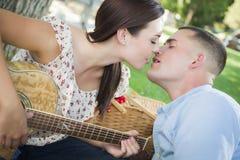 Küssen von Mischrasse-Paaren mit Gitarre im Park Stockfotografie