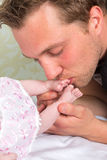 Küssende Babyfüße des Vaters Lizenzfreie Stockbilder