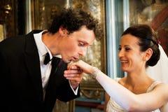 Küssende Brauthand des Bräutigams Stockfotos