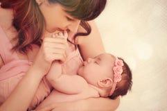 Küssende kleine Finger der mitfühlenden Mutter ihres netten schlafenden Babys g Lizenzfreie Stockfotos