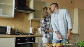 Küssende Umfassung der glücklichen jungen Paare und Plaudern in der Küche beim Frühstück zu Hause kochen stock footage