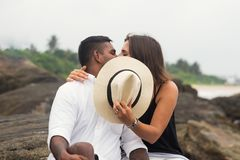 Küssendes Sitzen der jungen Mischrassepaare auf Stein Sie schließen Gesichter mit Hut Lizenzfreies Stockbild